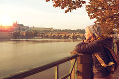 A young woman is looking at the sunset. Girl is looking at the sunset over a river Vltava in the city Prague. The old historical buildings are in the background Royalty Free Stock Photos
