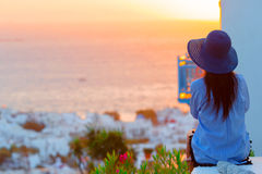 Young woman is looking at the sunset over a sea in famous village Mykonos with the old buildings in the background. Soft Royalty Free Stock Image