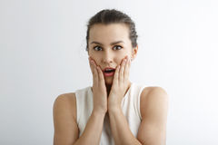 Young woman looking surprise against white background Royalty Free Stock Photography