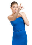 Young woman looking surprised. Attractive young woman in blue dress pointing up and looking surprised. Isolated on white background Stock Photo