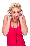 Young woman looking surprised listening to music Stock Photos