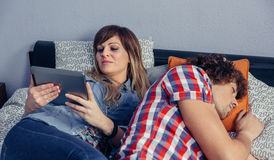 Young woman looking tablet and man sleeping in bed Stock Photography