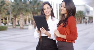 Young woman looking at a tablet outdoors stock video