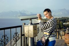 Young woman looking through telescope at sea Stock Photography