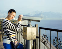 Young woman looking through telescope at sea viewpoint in Atatur Royalty Free Stock Photos