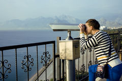 Young woman looking through telescope at sea viewpoint Royalty Free Stock Image