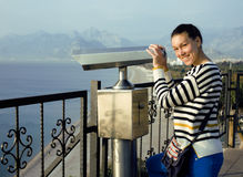 Young woman looking through telescope at sea viewpoint Stock Images