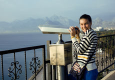 Young woman looking through telescope at sea viewpoint Royalty Free Stock Photo