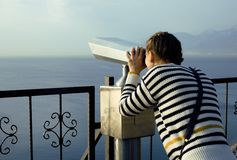 Young woman looking through telescope at sea Stock Photos