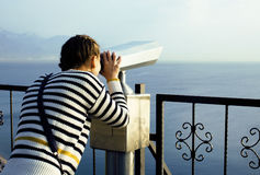 Young woman looking through telescope at sea viewpoint in Ataturk park Stock Photos