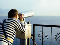Young woman looking through telescope at sea viewpoint in Ataturk park Stock Photo