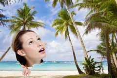 Young woman looking though hole at tropical beach Royalty Free Stock Photo