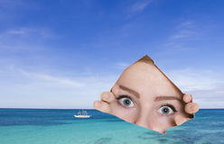 Young woman looking though hole at tropical sea Stock Image