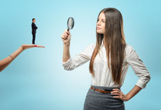 Young woman looking at tiny man with magnifying glass. Young women looking at a tiny men with a magnifying glass while he is standing on another women hand Stock Photography