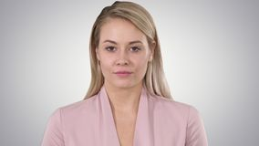 Young woman looking to camera and listening on gradient background. stock footage