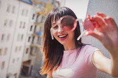 Young woman looking in to a camera through sunglasses royalty free stock image