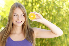 Young woman looking to Orangeslice. Young woman in front of a green natural background is looking to an orangeslice royalty free stock images