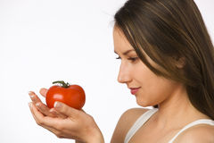 Young woman looking at tomato in her hands Royalty Free Stock Images