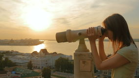 Young woman looking through tourist telescope, exploring city at sunset stock video footage