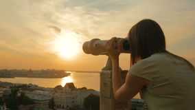 Young woman looking through tourist telescope, exploring city at sunset. Young woman looking through tourist telescope, exploring historical part of city. Sunset stock video footage