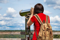 Young woman looking through tourist telescope Stock Photography