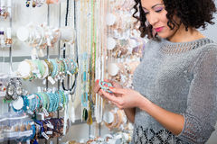 Young woman looking at trinket in shop Royalty Free Stock Image