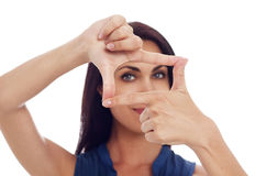 Young woman looking trough hands frame Stock Photography