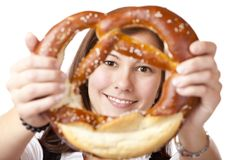 Young woman looking trough Oktoberfest Pretzel. Royalty Free Stock Photo