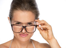 Young woman looking under eyeglasses Stock Photo
