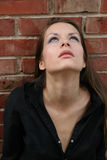 Young woman looking up. Head and shoulders portrait of a young woman with a serious expression looking upward.  Brick background Royalty Free Stock Photos