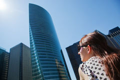 Young woman looking up at the business skyscrapers Royalty Free Stock Photo