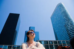 Young woman looking up at the business skyscrapers, sunny sky Royalty Free Stock Images