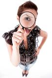 Young woman looking up with a magnifying glass Royalty Free Stock Images