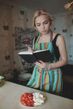 Young woman looking up in a recipes book Stock Photos