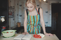 Young woman looking up in a recipes book Stock Image