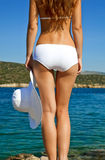 Young woman looking at water. Back of young woman holding white hat in her hand Stock Image