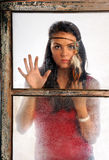 Young Woman Looking Through Window. Portrait of beautiful young woman wearing feather headband looking through old window Royalty Free Stock Photo