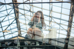 Young woman looking through window at airport Stock Images