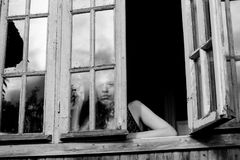 Young woman looking through window. Black-and-white photography Stock Photo