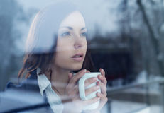 Young woman looking through the window Stock Photography