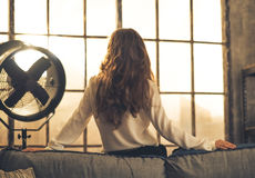Young woman looking in window in loft apartment. Rear view Royalty Free Stock Photo