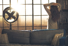 Young woman looking in window in loft apartment. Rear view Stock Photo