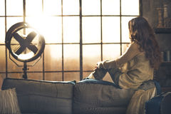 Young woman looking in window in loft apartment. Rear view Royalty Free Stock Images