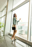 Young woman looking at window at modern airport terminal Royalty Free Stock Image