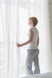 Young woman looking at window in the morning. Side view Stock Image