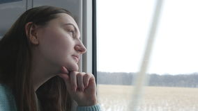 Young woman looking on window during riding on train. Profile of attractive girl traveling on railroad at winter time. Close up stock video