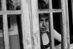 Young woman looking through window. Black-and-white photography Royalty Free Stock Image
