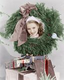 Young woman looking through a wreath with presents in front of her Stock Image