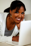 Young woman looking at you in front of her laptop Royalty Free Stock Images
