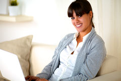Young woman looking at you in front of her laptop Stock Photography